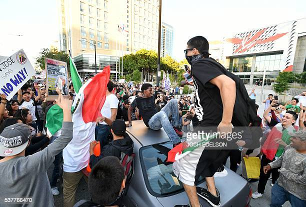Protesters climb atop a car stopped in traffic as a crowd marches near the venue where Republican presidential candidate Donald Trump was speaking...