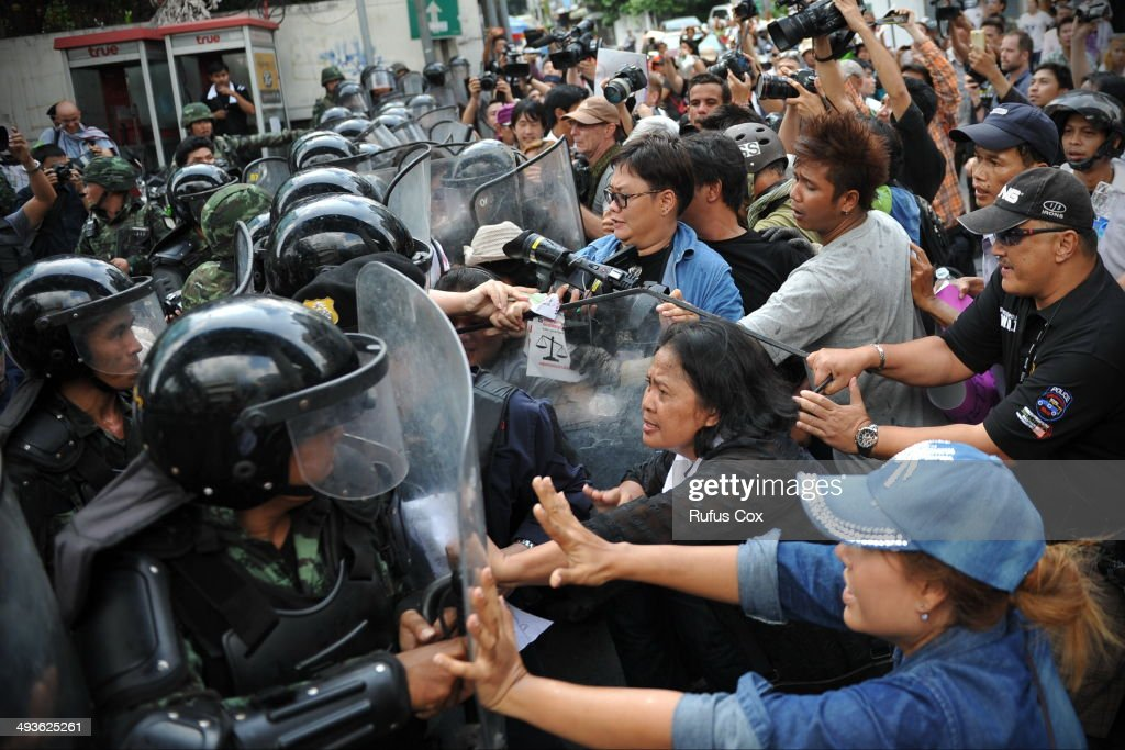 Protesters confront soldiers in riot gear blocking the route of an anti-coup march on May 24, 2014 in Bangkok, Thailand. Protesters defied a ban on public assembly by the ruling military to march on the city centre. The Thai capital has seen several anti-coup rallies since the military seized control on May 22.