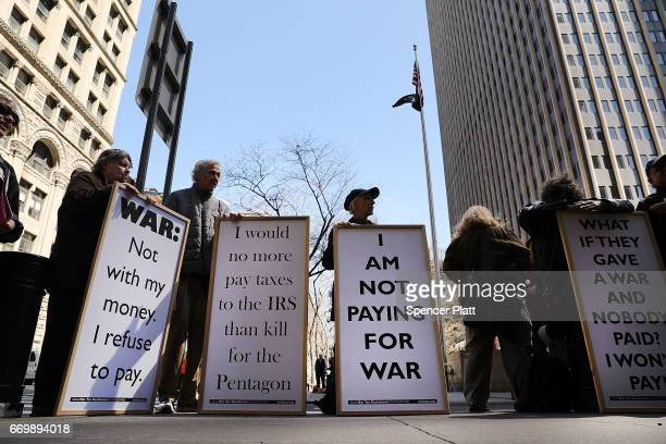 Protesters converge outside of the Internal Revenue Service on tax day in lower Manhattan to protest tax dollars being spent on the military on April...