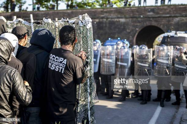 Protesters cover themselves with a screen as their shield against the policemen during the protest Hundreds of protesters are met in Lucca to show...