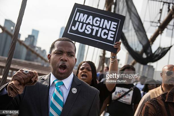 Protesters demanding further action against the police officers responsible in the death of Eric Garner march across the Brooklyn Bridge on May 29...