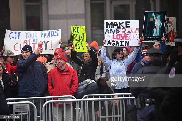 Protesters demonstrate as President Donald Trump and first lady Melania Trump walk in the inaugural parade after being sworn in at the 58th...