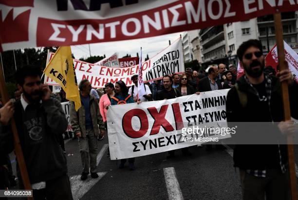 TOPSHOT Protesters demonstrate in Athens during a 24hour general strike against a new round of austerity cuts imposed by the country's international...