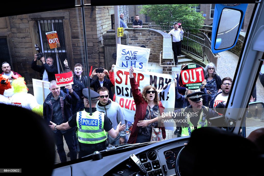 Protesters demonstrate in front of the Conservative bus (with Prime Minister Theresa May on board) as it departs the launch event for the Conservative Party general election manifesto in Halifax in northern England on May 18, 2017. British Prime Minister Theresa May will on May 18 promise to crack down on immigration from outside the European Union as she unveils the Conservative Party's manifesto. / AFP PHOTO / Dan Kitwood