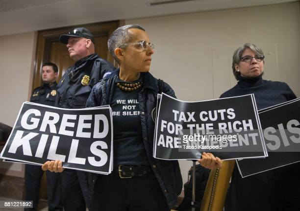 Protesters demonstrate near the full Senate budget committee markup of the tax reform legislation on Capital Hill November 28 2017 in Washington DC...