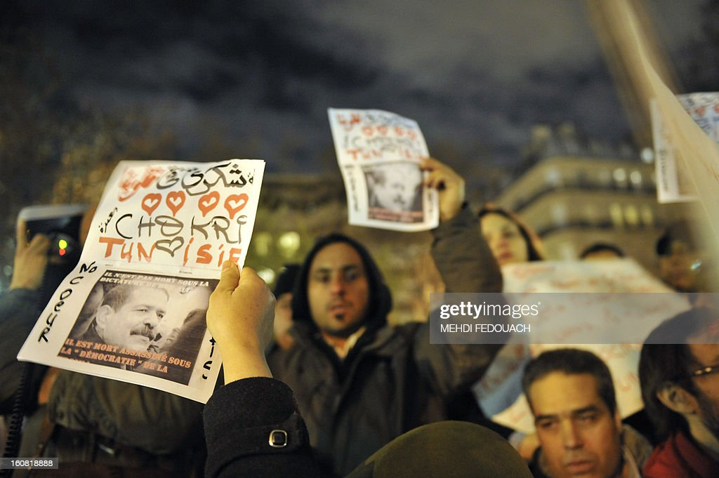 Protesters demonstrate on February 6, 2013 outside the Tunisian embassy in Paris against the killing today of prominent Tunisian opposition leader Chokri Belaid. Furious protesters on February 6 erected barricades in central Tunis and hurled rocks at police who tried to disperse them with tear gas in new clashes after the assassination of a prominent opposition figure. AFP PHOTO / MEHDI FEDOUACH