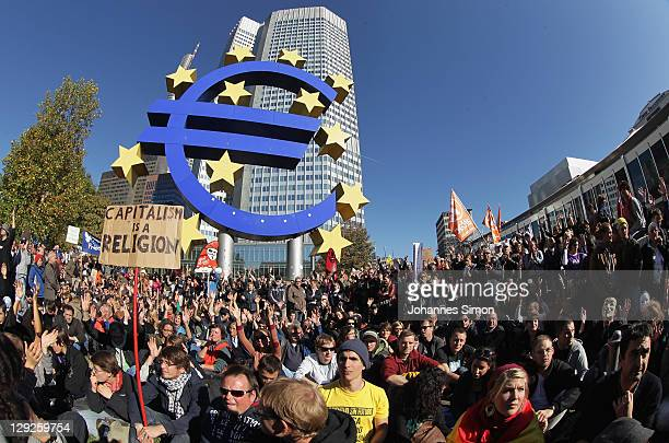 Protesters demonstrating against the influence of bankers and financiers sit on the floor next to the Euro symbol in front of the European Central...