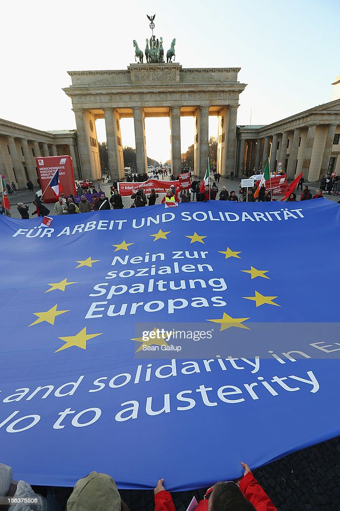 "Protesters demonstrating in solidarity with the economically-stricken nations of southern Europe hold taut a giant flag of the Euroepan Union with slogans that read: 'For Work And Solidairty, No To The Division Of Europe' and 'For jobs and solidarity in Europe, no to austerity' during a ""national day of action"" in front of the Brandenburg Gate organized by the German Federation of Labour Unions (DGB) on November 14, 2012 in Berlin, Germany. The DGB called for nationwide protests to coincide with strikes taking place today in Spain, Portugal, Greece, Italy and Belgium over government austerity measures meant to combat the ongoing Eurozone financial crisis."