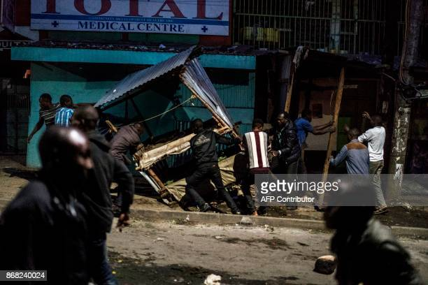 Protesters destroy a stall in the Mathare slums in Nairobi on October 30 2017 during demonstrations following the announcements of the results of the...