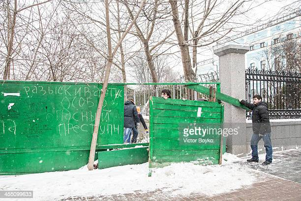 Protesters dismantling the wooden fence for reinforcing barricades on Independence Square on December 11 2013 in Kiev Ukraine Riot police today tried...