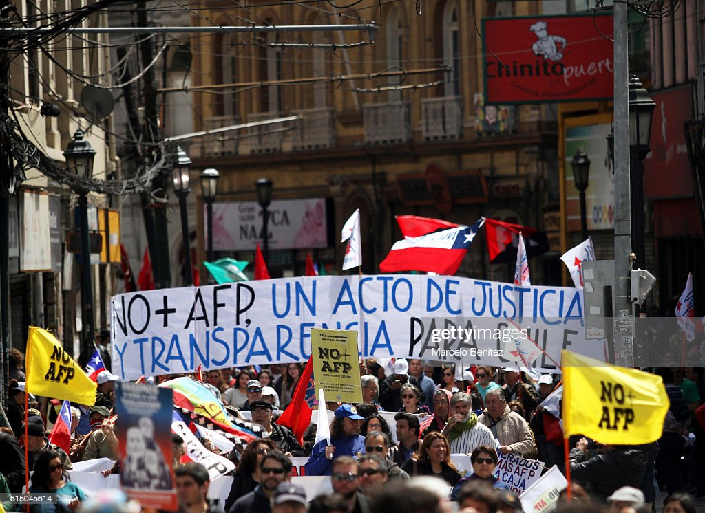 """Protesters display banners and shout slogans during a national demonstration against pension saving system organized by citizen movement """"'No AFP'"""" to demand decent pensions on October 16, 2016 in Valparaiso, Chile. The current Chilean pension system was imposed by former President of Chile Augusto Pinochet during his military dictatorship."""