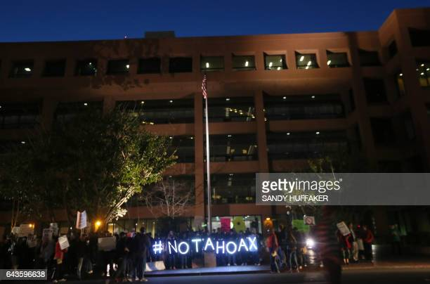 Protesters display lit signs during a rally against climate change in San Diego California on February 21 2017 The US Senate confirmed fossilfuel...