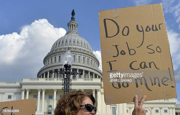 Protesters display placards during a demonstration in front of the US Capitol in Washington DC on October 1 2013 urging congress to pass the budget...
