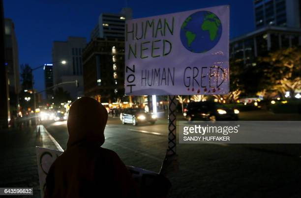 Protesters display signs during a rally against climate change in San Diego California on February 21 2017 The US Senate confirmed fossilfuel ally...