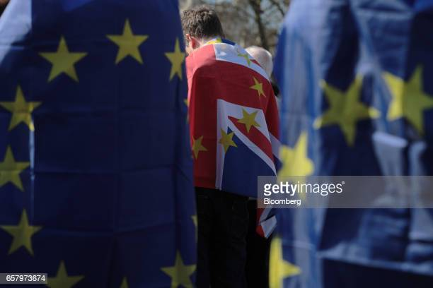 Protesters draped in European Union flags and a Union flag also known as Union Jack observe a minute of silence in memory of those who died in the...