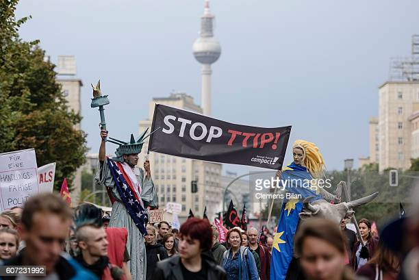 Protesters dressed as america and europe march to demonstrate against the TTIP and CETA free trade agreements on September 17 2016 in Berlin Germany...