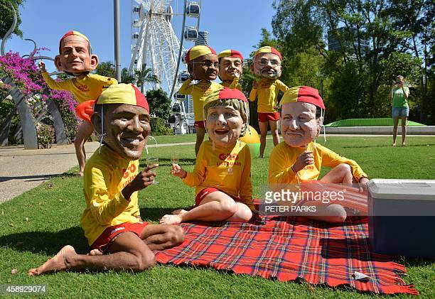 Protesters dressed as world leaders in fibreglass heads and dressed in lifesaver uniforms highlighting the need to halve global inequality pose on...