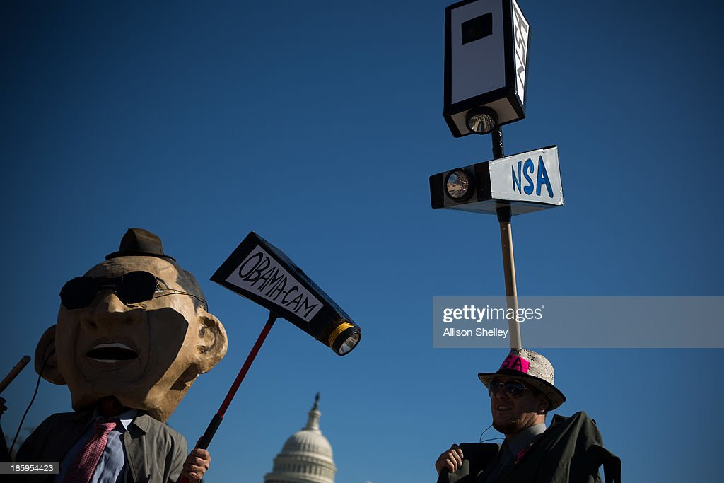 Protesters dressed up in costumes representing U.S. President <a gi-track='captionPersonalityLinkClicked' href=/galleries/search?phrase=Barack+Obama&family=editorial&specificpeople=203260 ng-click='$event.stopPropagation()'>Barack Obama</a> and an National Security Agency agent rally in front of the U.S. Capitol building during the Stop Watching Us Rally protesting surveillance by the U.S. National Security Agency, on October 26, 2013, in Washington, D.C. The rally began at Union Station and included a march that ended in front of the U.S. Capitol building and speakers such as author Naomi Wolf and former senior National Security Agency senior executive Thomas Drake.