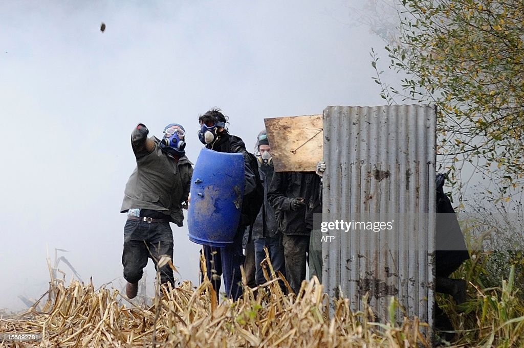 Protesters face French riot police on November 24, 2012 as they seek to evict squatters from protected swampland where Prime Minister Jean-Marc Ayrault wants to build a new airport. Clashes between police and protesters resumed at Notre-Dame-des-Landes, outside the western city of Nantes, as officers fired tear gas and squatters threw stones and glass bottles at them in return.