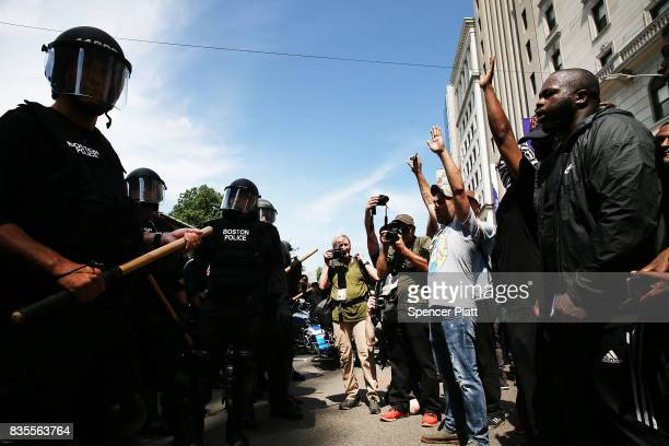 Protesters face off with riot police escorting conservative activists following a march in Boston against a planned 'Free Speech Rally' just one week...