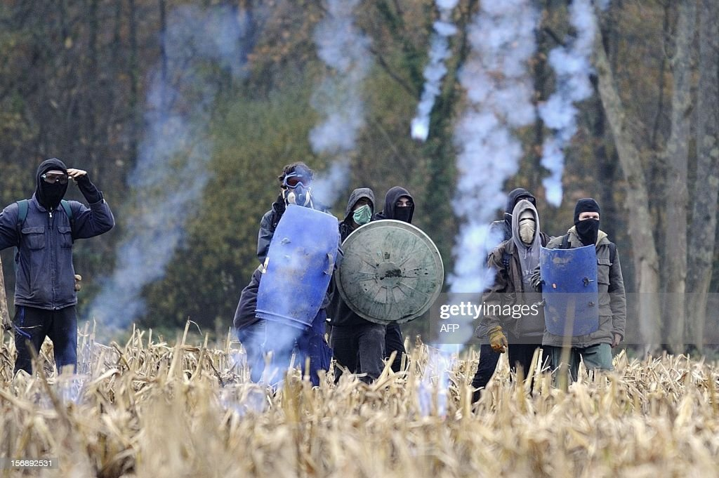 Protesters face on November 24, 2012 French riot police, seeking to evict squatters from protected swampland where Prime Minister Jean-Marc Ayrault wants to build a new airport. Clashes between police and protesters resumed at Notre-Dame-des-Landes, outside the western city of Nantes, as officers fired tear gas and squatters threw stones and glass bottles at them in return.