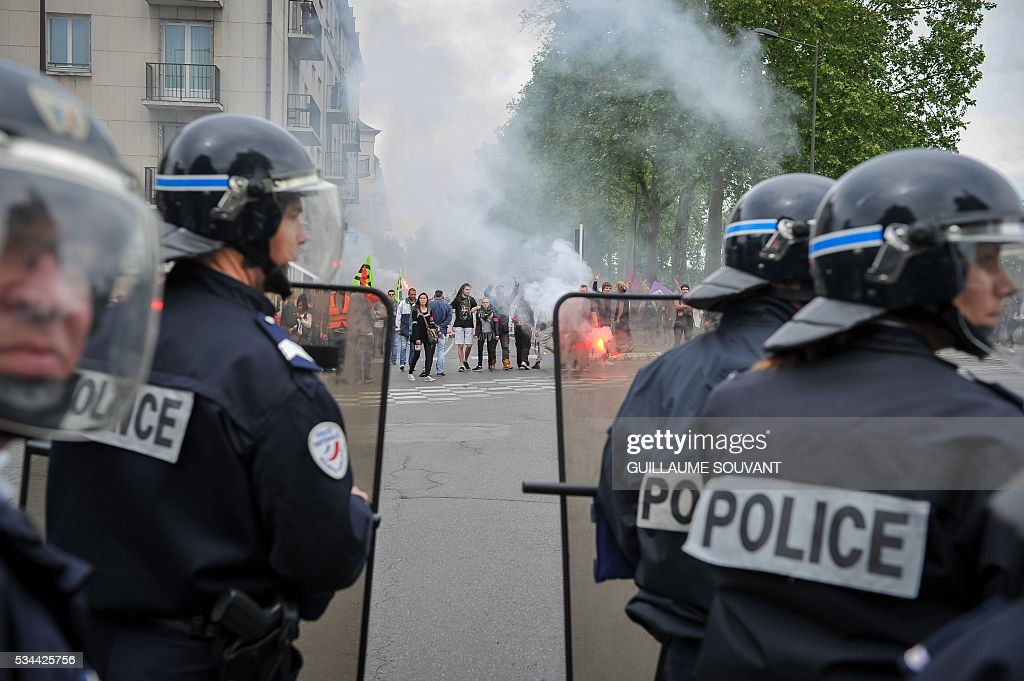 Protesters face riot police during a protest against the government's planned labour law reforms on May 26, 2016 in Tours, Central France. The French government's labour market proposals, which are designed to make it easier for companies to hire and fire, have sparked a series of nationwide protests and strikes over the past three months. / AFP / GUILLAUME
