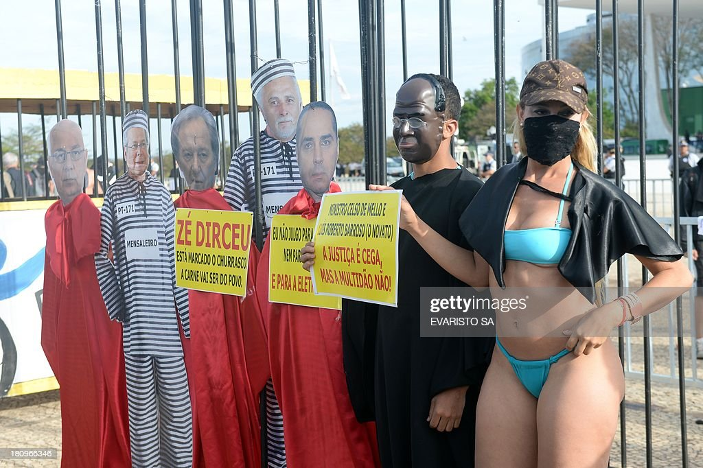 Protesters fancy dressed as the president of Brazil's Supreme Court Joaquim Barbosa (2nd-R) and popular singer 'Bandida' (R) pose along dummies of accused during a protest against the approval of the review of the appeals that will result in a new trial for 11 of the accused in the Mensalao scandal, in Brasilia on September 18, 2013. The session was held to review the appeals of those convicted for diverting at least $35 million in public money to bribe legislators to get their support for former President Luiz Inacio Lula da Silva's minority government after he took office in 2003. AFP PHOTO/Evaristo Sa