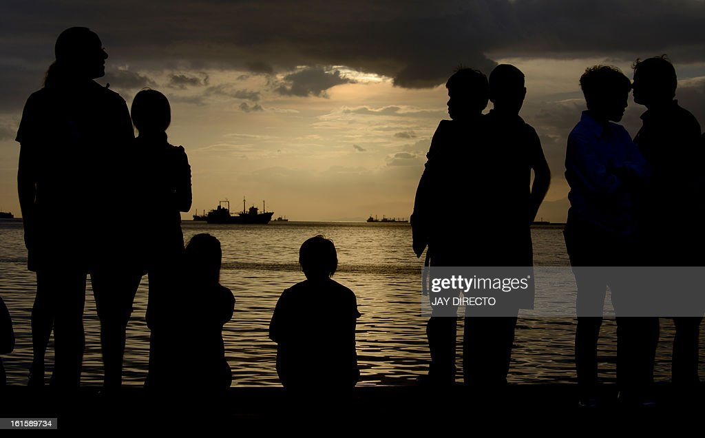 Protesters flock to the water front to watch a cloudy sunset in Manila Bay on February 12, 2013. Hundreds of Filipinos converged on the Philippine capital's main bay front Tuesday for a unique 'sunset watch' protest aimed at stopping what they said would be a disastrous reclamation project. AFP PHOTO / Jay DIRECTO