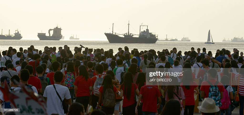 Protesters flock to the water front to watch the sunset in Manila Bay on February 12, 2013. Hundreds of Filipinos converged on the Philippine capital's main bay front Tuesday for a unique 'sunset watch' protest aimed at stopping what they said would be a disastrous reclamation project. AFP PHOTO / Jay DIRECTO