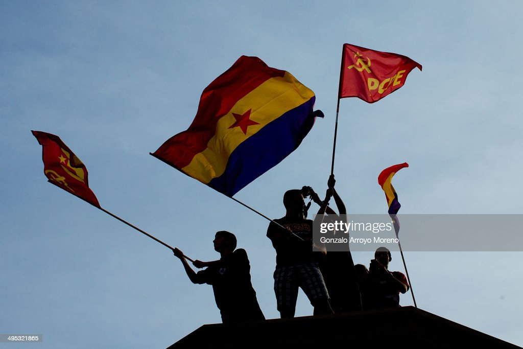 Protesters flutter Republican and Comunist Party flags in support of a referendum on whether Spain should return to a Republic at Sol Gate square on June 2, 2014 in Madrid, Spain. King Juan Carlos of Spain has renounced the throne after 39 years and will be succeeded by his son, Prince Felipe.