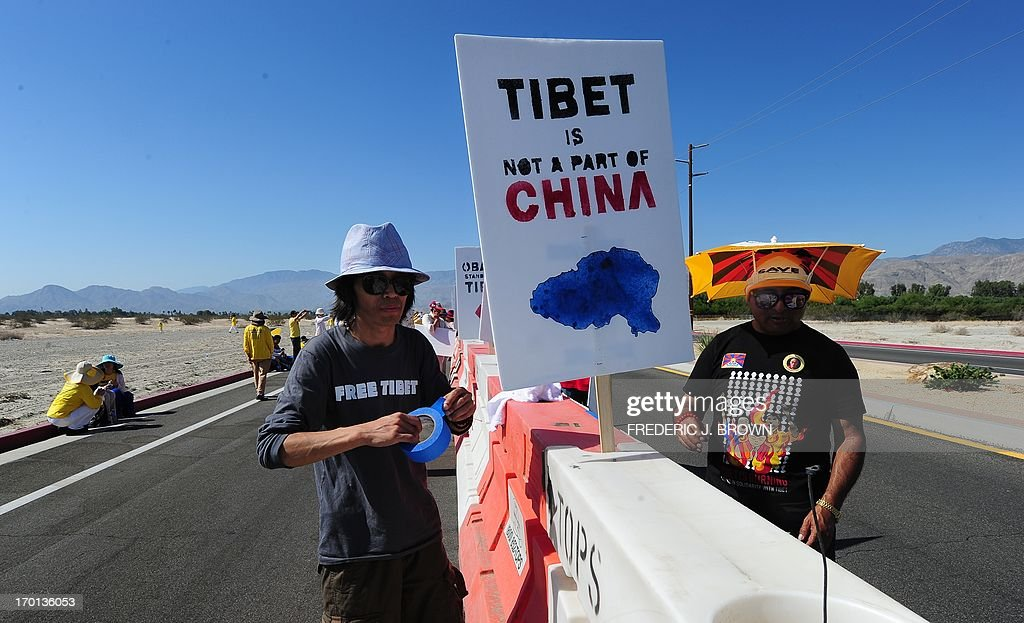 Protesters for the Tibetan cause setup their placards on a barricade in a cordoned off protest zone across from where President Barack Obama is due to meet his Chinese counterpart Xi Jinping in the California desert community of Rancho Mirage, a little over 100 hundred miles east of Los Angeles, on June 7, 2013, where they were joined by Falun Gong practioners in protesting the brutal repression of China's ruling Communist Party. Xi, the Chinese leader arrived in southern California the previous evening and stayed in a nearby hotel, according to the local Desert Sun newspaper, ahead of what was planned as an unusually relaxed US-China summit. AFP PHOTO/Federic J. BROWN