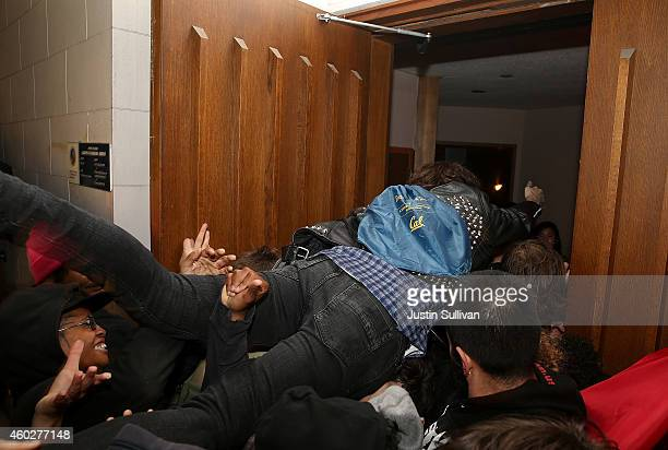 Protesters force their way into Wheeler Hall to disrupt The Berkeley Forum presentation during a demonstration over recent grand jury decisions in...