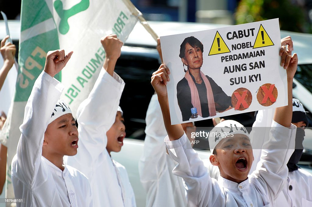 Protesters from a hardline Muslim group demand to revoke the Nobel Peace Prize award from Aung San Suu Kyi (pictured on placard) during an anti-Myanmar protest in Solo, Central Java, on May 3, 2013. The protest highlighted the growing anger in Muslim-majority Indonesia over a string of religious clashes in largely-Buddhist Myanmar, that have left many minority Muslims dead and tens of thousands displaced. Meanwhile, two Indonesians were detained over a plot to bomb the Myanmar embassy in Jakarta, officials said. AFP PHOTO / ANWAR MUSTAFA