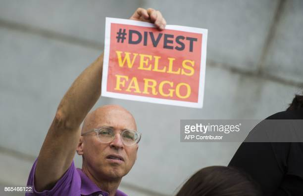 Protesters from DC Divest hold up signs during a Divest the Globe demonstration in Washington DC on October 23 2017 DC Divest seeks to get the...