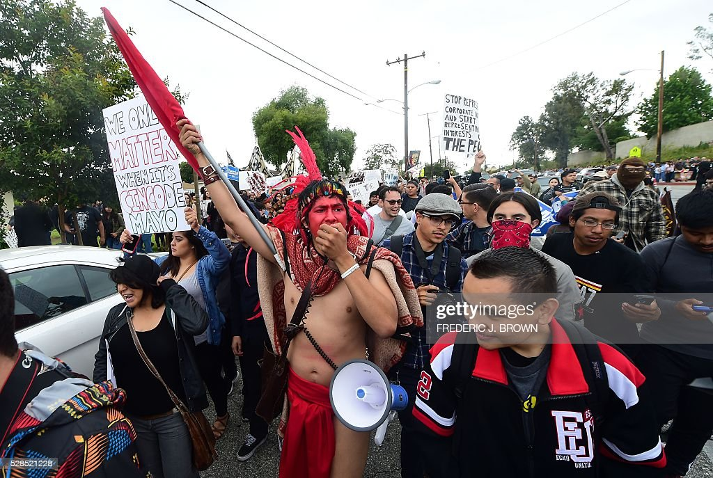 Protesters from Latino and Community groups make their way to East Los Angeles College in Monterey Park, California ,on May 5, 2016, to protest US Democratic presidential candidate Hillary Clinton. Clinton campaigned in the Los Angeles ahead of California's June 7 primary. / AFP / FREDERIC