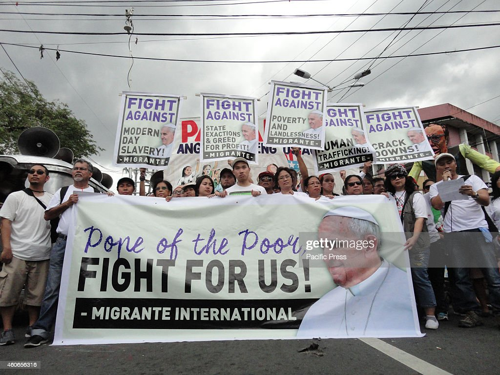 Protesters from migrant workers' group Migrante read an open letter addressed to Pope Francis during a protest near Malacanang presidential palace...