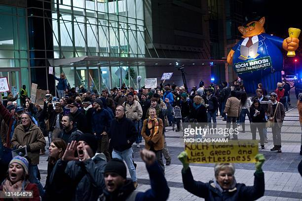 Protesters from Occupy DC march past the Washington Convention Center during a demonstration against the billionaire conservative donor Koch brothers...
