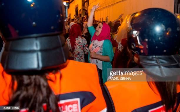 Protesters from Rif movement 'Hirak' shout slogans as they face off with police during a demonstration against the government in Al Hoceima city on...