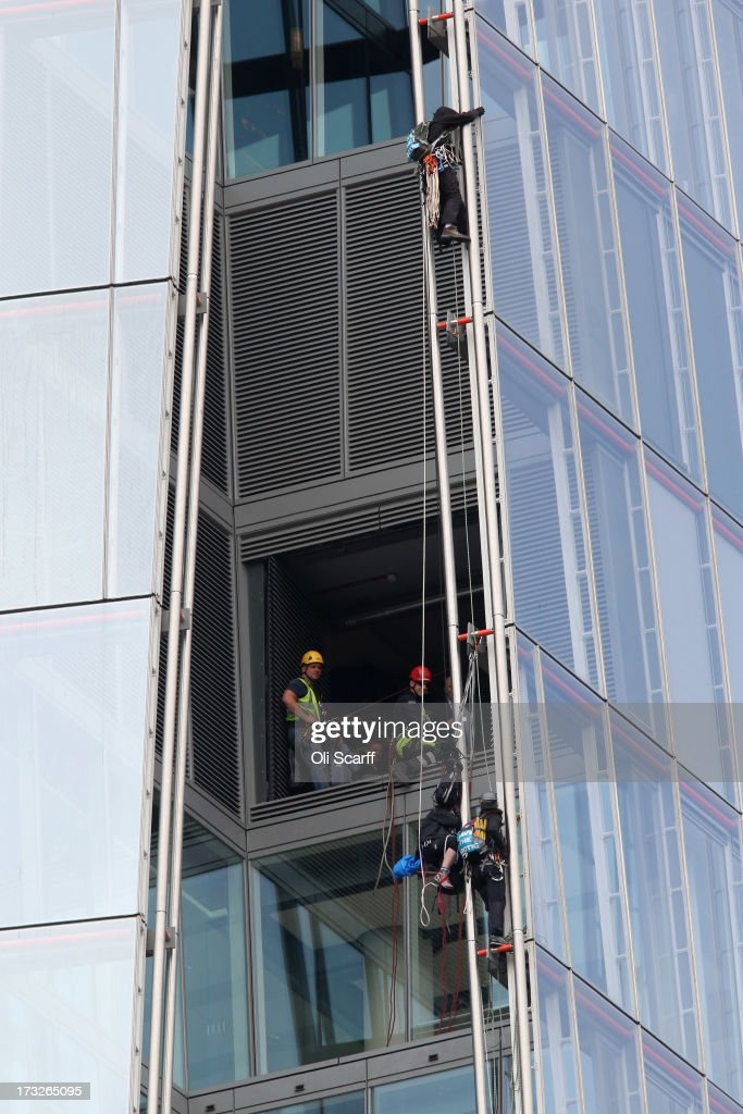 Protesters from the environmental charity Greenpeace are watched by workers as they attempt to scale the tallest building in western Europe, The Shard, in a bid to unveil a giant banner from the top on July 11, 2013 in London, England. The six female protesters began their unauthorised ascent of the 310 metre high skyscraper shortly after 4am with the intention of highlighting the environmental damage caused by drilling for oil in the Arctic by Shell.