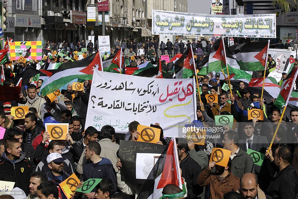 Protesters from the Islamic Action Front and other opposition parties hold signs read 'Boycotting' during a protest in Amman on January 18, 2013. Some 2,000 protesters including Islamists, youths and leftists held a sit-in the Jordanian capital, rejecting as 'cosmetic' a general election due to be staged next week. AFP PHOTO KHALIL MAZRAAWI