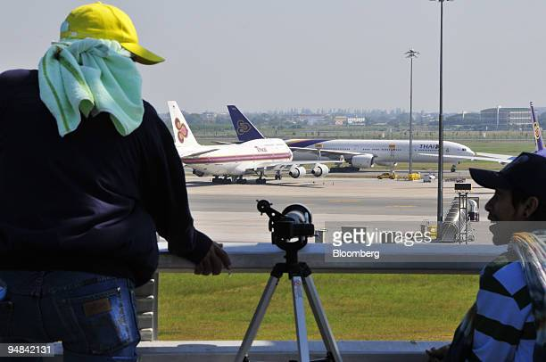 Protesters from the People's Alliance for Democracy use a telescope to watch for movements around parked aircraft at Suvarnabhumi International...