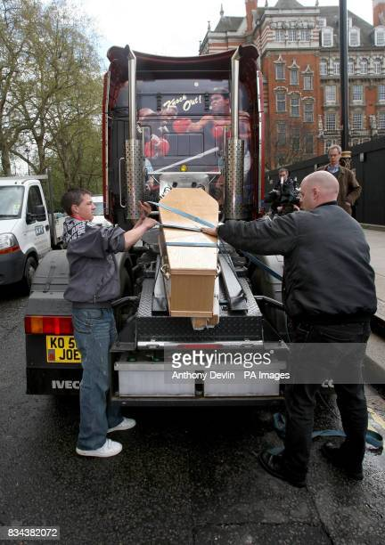 Protesters from the Transaction 2007 protest group secure a coffin to a lorry outside the Houses of Parliament London as part of a protest against...