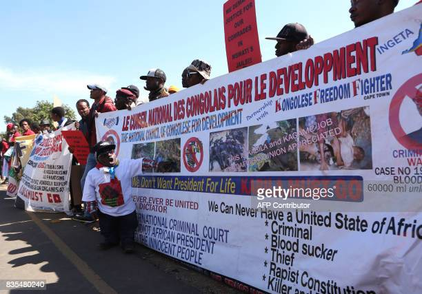 Protesters from various Southern African Development Community countries holds a banner as they demonstrate near the entrance to Department of...