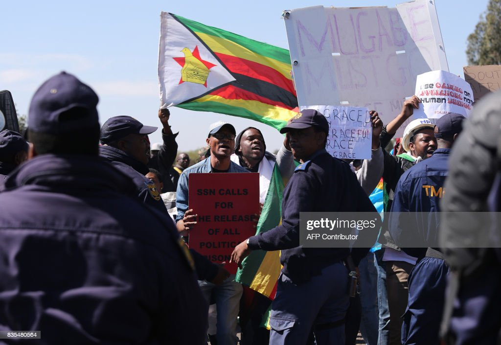 Protesters from various Southern African Development Community (SADC) countries demonstrate near the entrance to Department of International Relations and Cooperation where the SADC Summit is being held in Pretoria on August 19, 2017. The protesters are demanding for the Democratic Republic of Congo (DRC) President Joseph Kabila to step down, and also calling on South Africa to set an example in the handling of the Zimbabwe's first lady Grace Mugabe who is seeking diplomatic immunity for an alleged assault in South Africa on a a 20-year-old model. / AFP PHOTO / Phill Magakoe