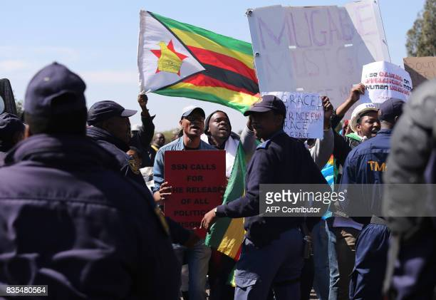 Protesters from various Southern African Development Community countries demonstrate near the entrance to Department of International Relations and...