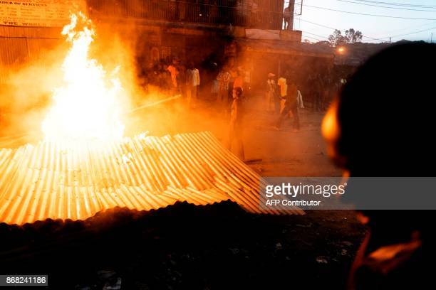 Protesters gather around a burning barricade in the Mathare slums in Nairobi on October 30 2017 during demonstrations following the announcements of...