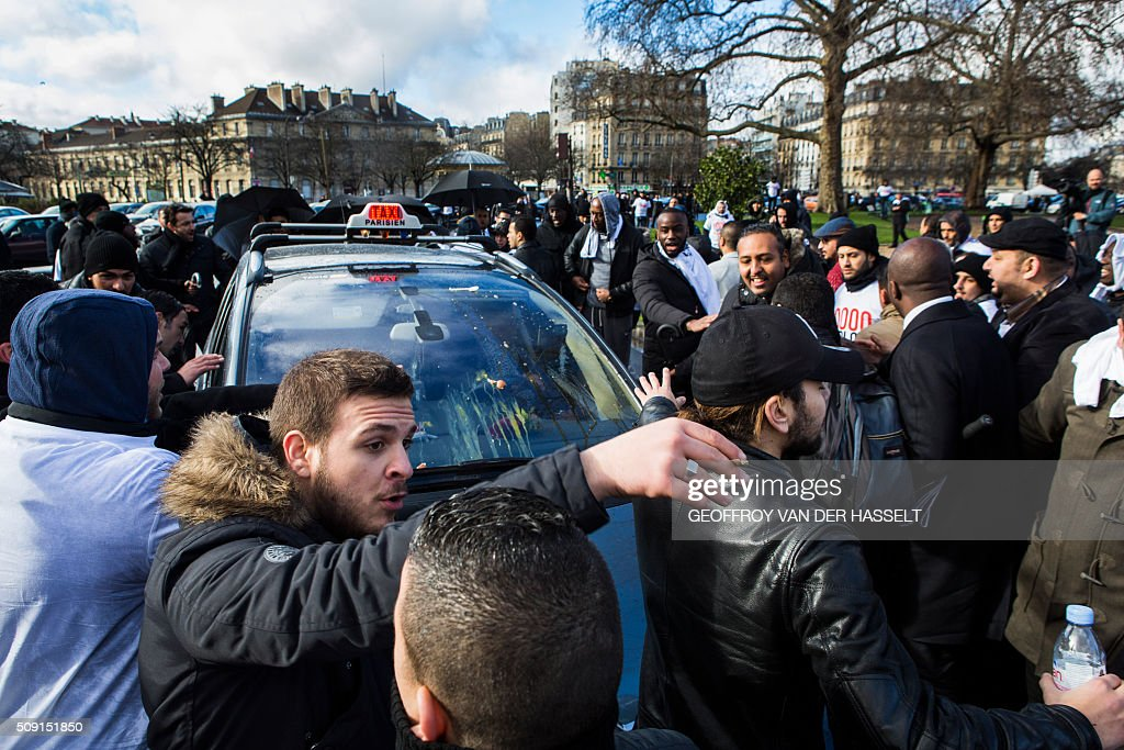 Protesters gather around a taxi that received eggs on its windshield on the Place de la Nation in Paris on February 9, 2016, during a demonstration by non-licensed private hire cab drivers, known in France as VTC (voitures de tourisme avec chauffeur or tourism vehicles with chauffeur). VTC drivers continued a fifth day of protests on February 9 against measures granted by the French prime minister to taxi drivers. / AFP / Geoffroy Van der Hasselt