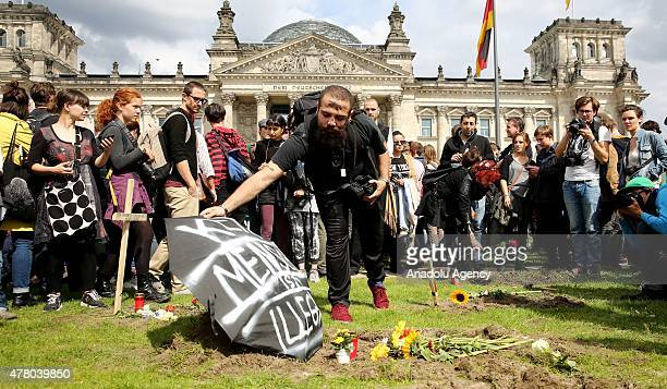 Protesters gather around symbolic graves after entering the fence in front of the German Parliament Building on June 21 2015 in Berlin Germany A...