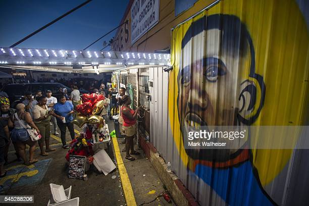 protesters gather in front of a mural painted on the wall of the convenience store where Alton Sterling was shot and killed July 6 2016 in Baton...