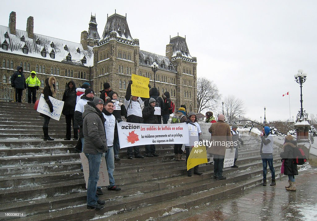 Protesters gather in front of the Canadian parliament in Ottawa on January 29, 2013 as thousands of immigrants pressed Canada's government to fast-track their permanent residency applications, saying undue delays have put their lives on hold for years. They came to Canada from France, Italy, Morocco and elsewhere, paid thousands of dollars in fees and filled out lengthy forms. AFP PHOTO/Michel COMTE